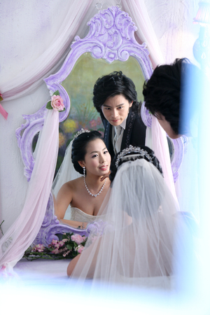 mirror image: Asian bride and groom in wedding dresses posing in a studio with reflection on mirror Stock Photo