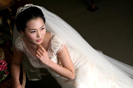 椅子に座っているようにスタジオでポーズウェディングドレスでアジアの花嫁のクローズアップショット 写真素材