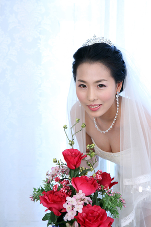 Close up shot of Asian bride in wedding dresses posing in a studio with flowers