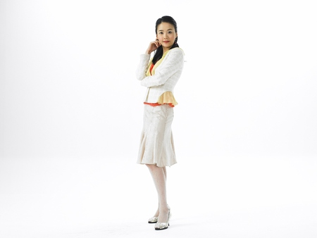 Asian woman fashion model posing in a studio as wearing white formal skirt outfit