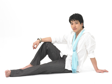 Asian man model fashion isolated in white wearing white shirt as sitting on floor with laptop