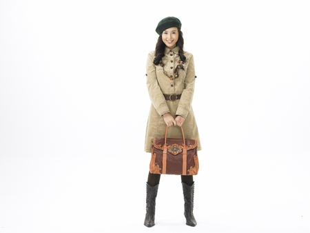 Young Asian female fashion model posing in a studio wearing trenchcoat with beret hat