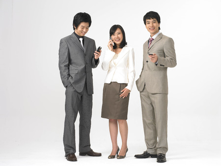 Two Asian men and a woman in formal business suits posing in a studio with cell phones Stock Photo