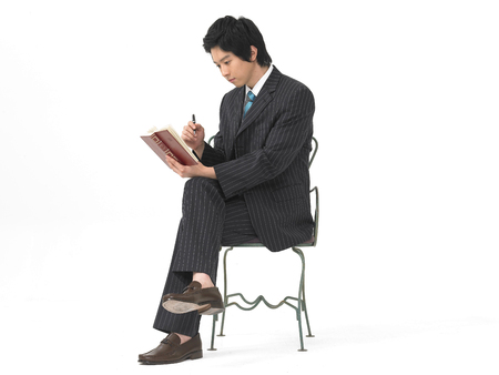 Asian man model formal business look fashion posing in a studio as sitting on chair with a book