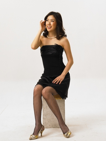 Asian woman fashion model posing in a studio as wearing black cocktail dress and fishnet stockings Stock Photo