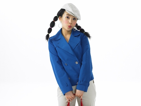 Asian woman fashion model posing in a studio as wearing white trousers outfit with a purse Stock Photo