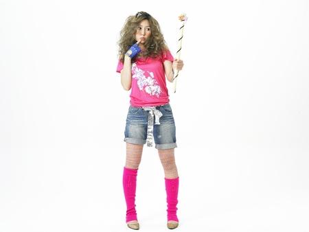Asian woman fashion model posing in a studio as wearing flower pattern shirt with pink leg warmers Stock Photo
