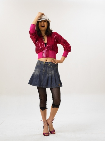 Asian woman fashion model posing in a studio as wearing pink spangle jersey and white pedora