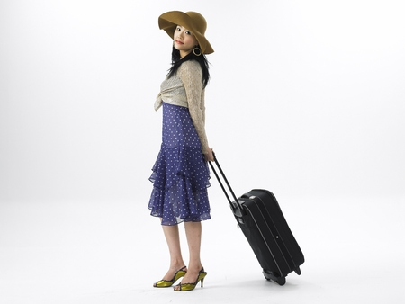 Asian woman fashion model posing in a studio as wearing vacation look beach dress with floppy hat with travle luggage bag