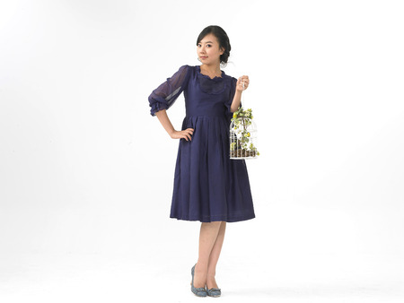 Asian woman model formal look fashion isolated in white wearing navy blue dress with bird cage prop Stock Photo