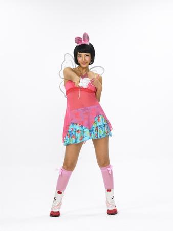 スタジオでモデルを装うの天使の翼を持つウサギのような着飾った若いアジア女性ファッションします。