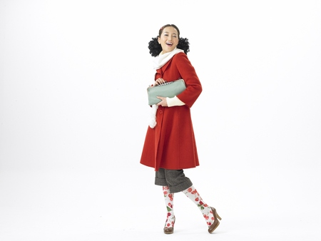 Young Asian female fashion model posing in a studio wearing winter outfit