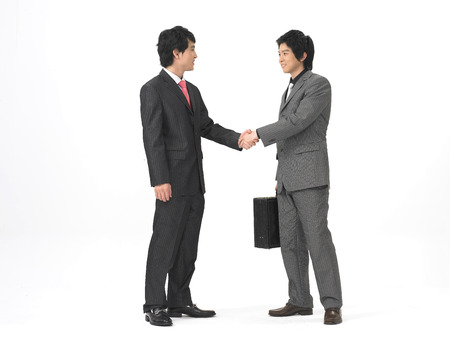 Two Asian men in formal business suits posing in a studio as handshaking with each other