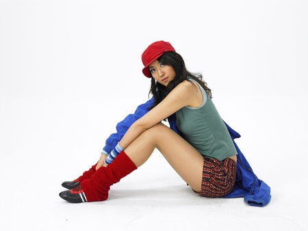 Young Asian female fashion model posing in a studio wearing cozy short pants outfit with leg warmers