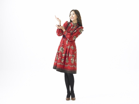 Young Asian female fashion model posing in a studio wearing ethnic dress