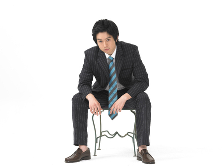 Asian man model formal business look fashion posing in a studio as sitting on chair