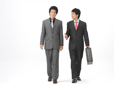Two Asian men in formal business suits posing in a studio in walking motion Stock Photo