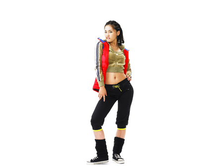 Young Asian female fashion model posing in a studio wearing sporty outfit with leg warmers