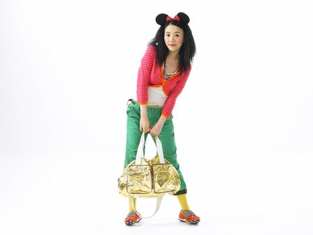 Asian woman fashion model posing in a studio as wearing colorful outfit with mickey mouse ear headband
