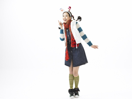 Young Asian female fashion model posing in a studio wearing winter outfit and snowman headband Stock Photo