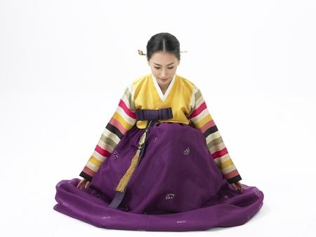 Bowing으로 스튜디오에서 포즈 보라색 치마와 전통 의상을 입고 한국 여자