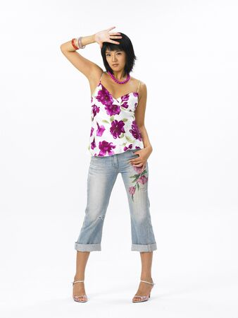 Young Asian female fashion model posing in a studio wearing flower pattern summer outfit Stock Photo