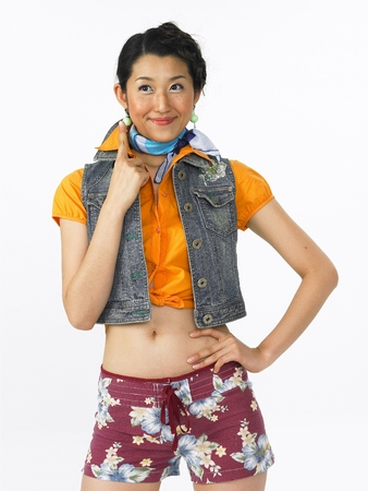 Young Asian female fashion model posing in a studio wearing beach look with shorts Stock Photo