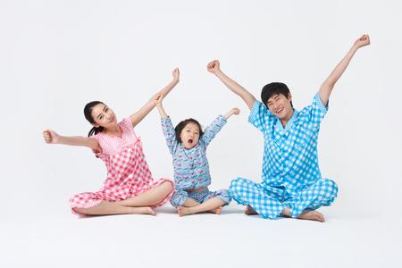 両親と若い子供たちが一緒にパジャマでストレッチ家族の時間を過ごす