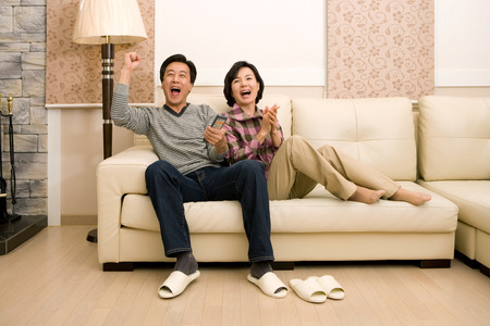 Mid-aged married Asian couple spending time together as watching TV in the living room