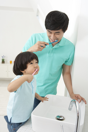 Father and son spending family time together as brushing teeth together Stock Photo