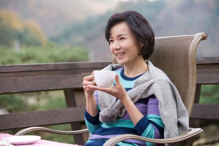 Asiatische Frau von mittlerem Alter, die als Kaffee im Patio trinkend aufwirft Standard-Bild