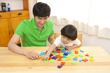 Father and son spending family time together with letter blocks