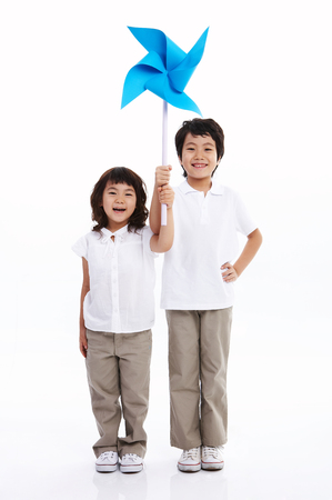 Little Asian boy and girl in white shirts posing with a paper windmill - isolated on white Stock Photo
