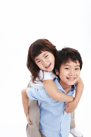 Little Asian boy giving his sister piggy back - isolated on white
