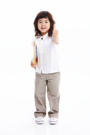 Little Asian girl holding books with cheerful pose - isolated on white
