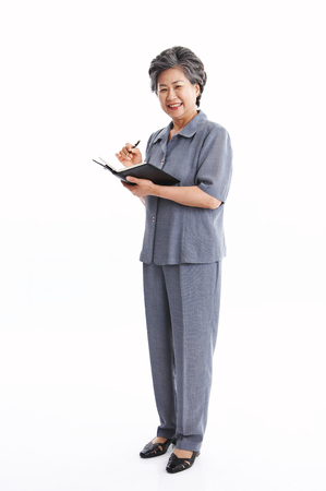 Asian middle aged woman writing on the scheduler - isolated on white