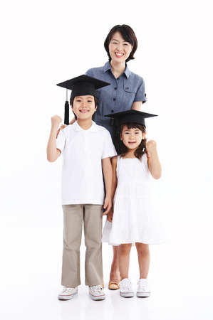 Asian boy and girl wearing graduation cap and posing with their mom - isolated on white