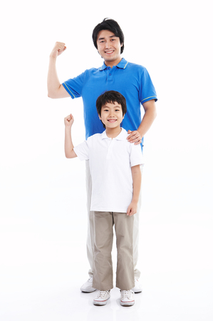 Asian dad and son showing their arm muscle - isolated on white