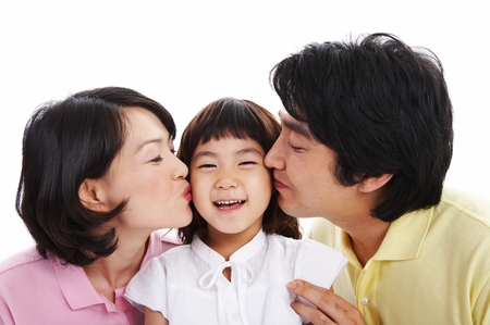 Asian parents kissing on their little girls cheeks - isolated on white Stock Photo