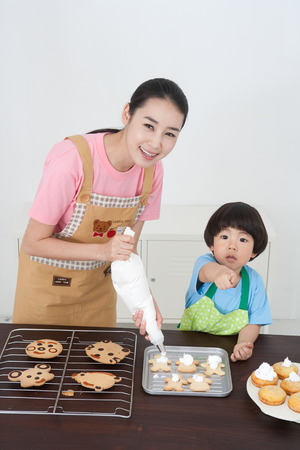 Asian Mom And Son Decorating Cupcakes With Icing Stock Photo, Picture And  Royalty Free Image. Image 85620437.
