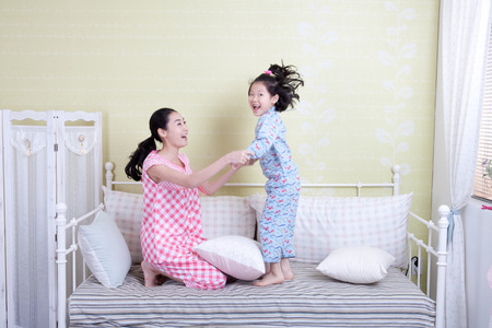 Happy Asian family before bed time, having fun on bed Banco de Imagens