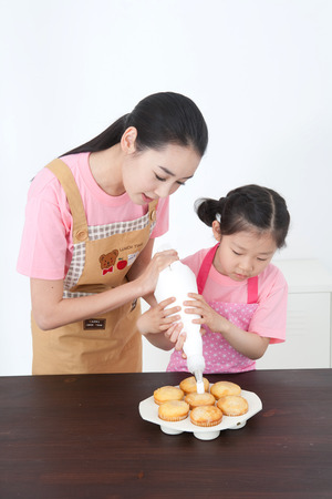 asian mom and daughter decorating cupcakes with icing photo - Woman Decorating Cupcakes