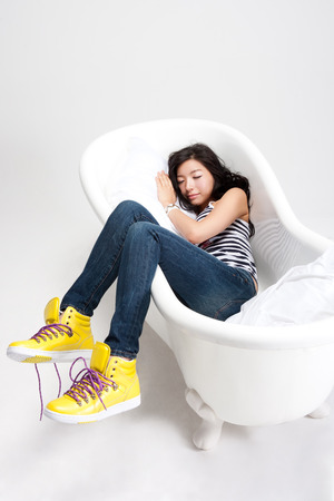 bath: Attractive Asian woman in bathtub isolated on white