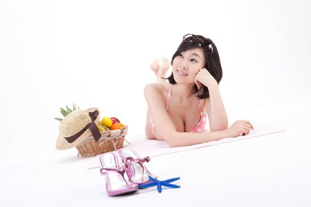 Asian bikini swimsuit woman laying down on mat with picnic basket isolated on white