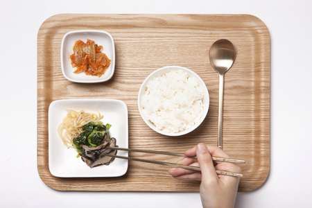 Korean food, a bowl of rice, kimchi, steamed beansprouts, spinach and mushroom, metal spoon and chopsticks - isolated on white