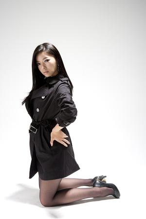 Mujer con estilo asiático que se ríe en el suelo aislado en blanco Foto de archivo - 86276325