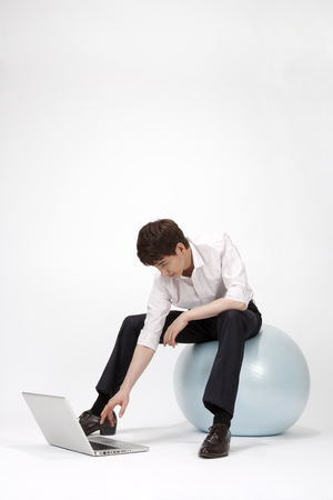 Asian young man using tablet pc on flexible ball isolated on white Stock Photo