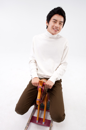 Asian young man riding hobby horse isolated on white