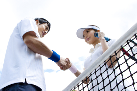 Close up from below Asian sporty couple shaking hands in tennis court Stock Photo