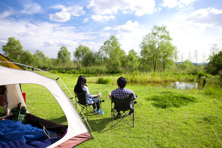 Rear view of Asian couple on chair in camping in the forest